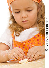 Little girl making cookies series - folding the dough over...