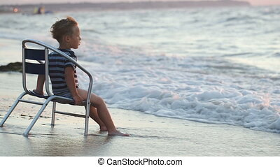 Boy sitting on the chair by sea, waves washing his feet