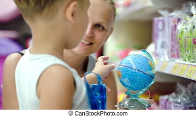 Mother and son with small globe in the shop - Mother and son...