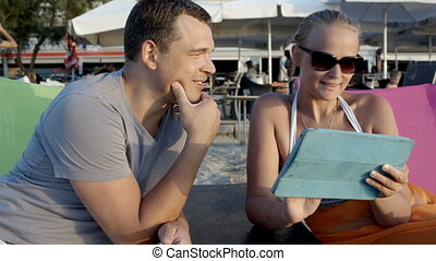 Man and woman with tablet computer on the beach - Young man...