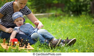 Mother and son spending time on the lawn in countryside