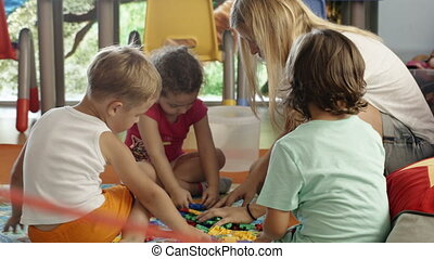 Group of children playing with schoolmaster - Group of three...