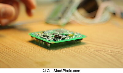 Soldering pads on the device - Scientist soldering pads on...