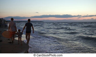 Family of three walking barefoot along the shore