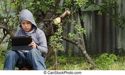 Teenager using tablet computer in the yard - Dolly shot of a...