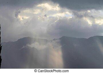 Sun rays through the clouds on Garda lake
