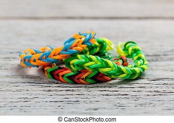 Loom bands bracelet on wooden background