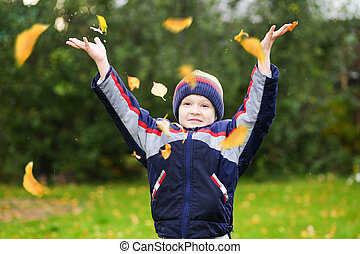 Happy boy throws the autumn leaves in the air.