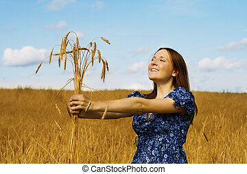 woman holding bundle of wheat ears