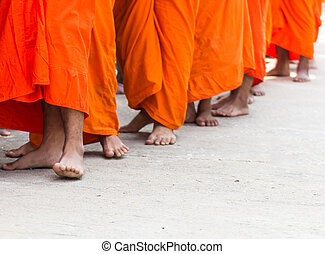 Monks walking on a street for receive food offerings on morning