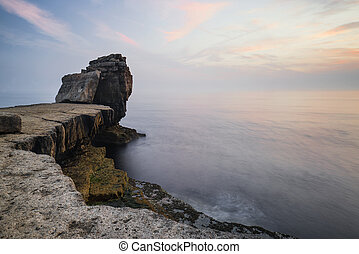 Beautiful rocky cliff landscape with sunset over ocean