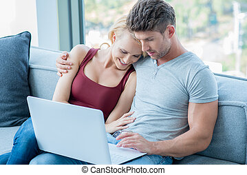 Loving couple surfing the web on a laptop computer as they...