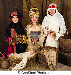 Three wise men in nativity scene - Three girls playing as...