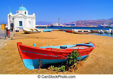 Mykonos harbor - Old boat and traditional blue dome church...
