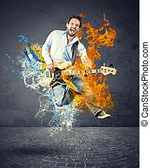 Boy with bass guitar jumps with fire and water