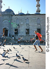 Blonde girl disturbing the pigeons on Istanbul square of the...