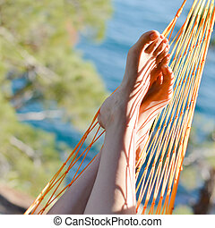 closeup picture of feet in a hammock on the beautiful summer...