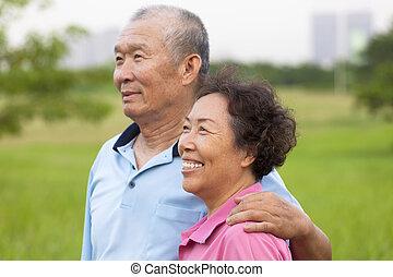 Happy elderly seniors couple in the park.