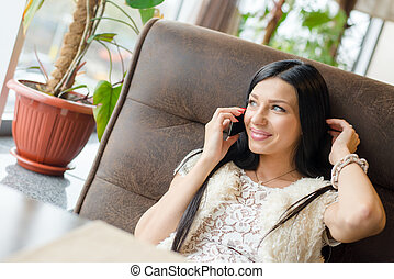 image of beautiful brunette woman sexy girl having fun sitting in a restaurant lounge or coffee shop and talking on mobile cell phone happy smiling touching her hair & looking at copy space window