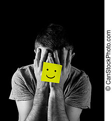 young man suffering depression and stress alone with smiley...