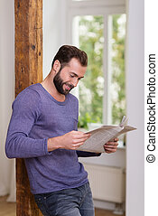 Relaxed man standing reading a newspaper while leaning...