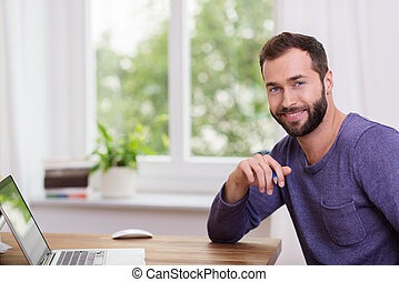 Good-looking bearded man in a home office sitting at a table...