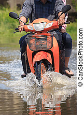 Splash by a motorcycle as it goes through flood water