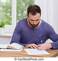 Man working on paperwork at home writing notes on a sheet of...
