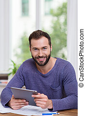 Smiling happy man working with a tablet