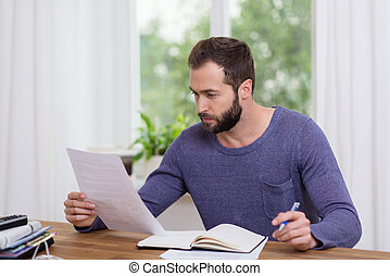 Man sitting doing paperwork in a home office - Attractive...