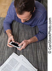 Man sending a text message on his smartphone