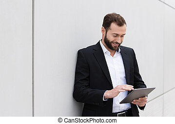 Businessman using a tablet computer - Businessman standing...