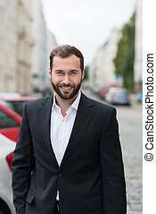 Handsome bearded businessman with a friendly smile standing...