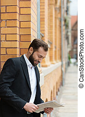 Businessman standing outdoors reading - Businessman standing...