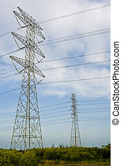 large power line towers in a green field against a blue sky