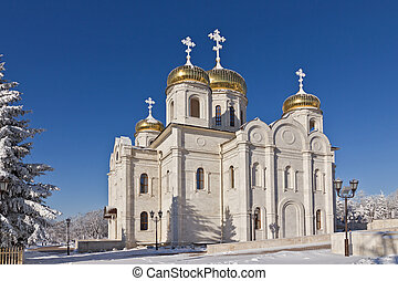 Orthodox temple with golden domes of white stone and covered...
