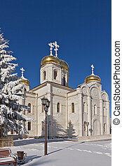 Orthodox temple of white stone dusted with snow against the...