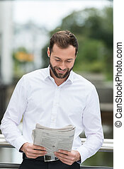 Man smiling as he reads the newspaper outdoors while taking...