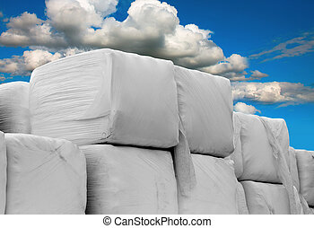 Heap of cubic hay bales wrapped in white plastic on blue sky