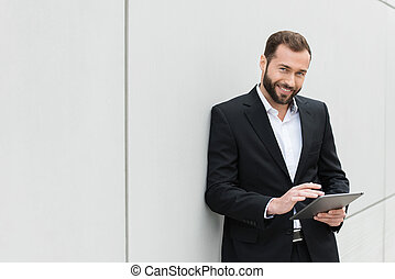 Successful businessman standing using a tablet to access the...