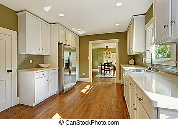 Green kitchen room with white storage combination, steel...