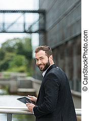 Attractive man standing on an urban bridge with a tablet...