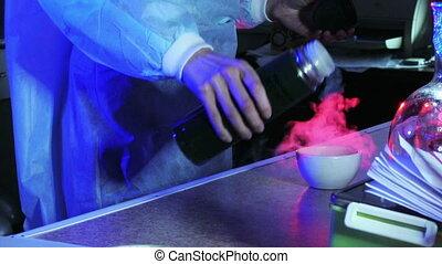 Laboratory - Man in a dark laboratory pouring liquid...