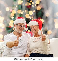 happy senior couple in santa helper hats - family, holidays,...