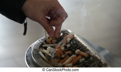 person extinguishes a stub of a cigarette and leaves in an...