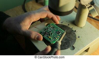 Scientist solder, looking through a