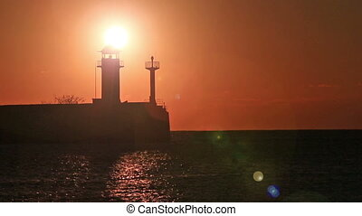 Sunrise against a beacon in Yalta, the Crimea