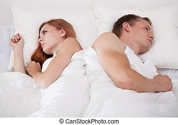 Couple lying back to back - Couple lying in bed back to back