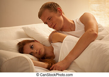 Young couple lying in bed - Image of young couple lying in...