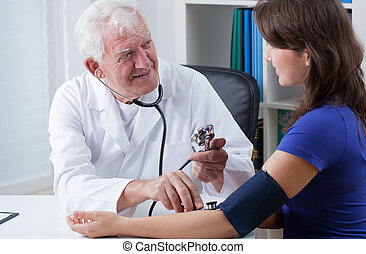 General practitioner taking blood pressure of young woman